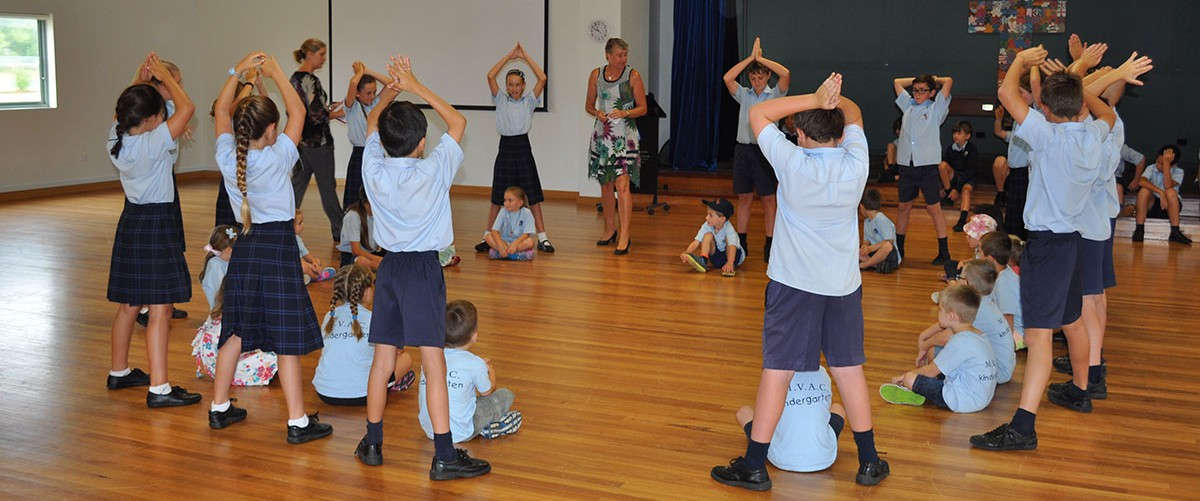 A group of primary school children play a game in the MVAC hall. Regular interaction between students of all ages is an important part of the school life style.