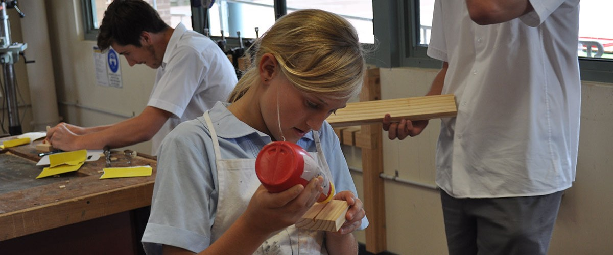 A high school student makes use of the school's timber workshop.