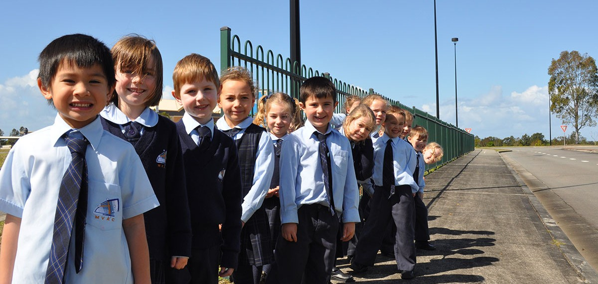 A group of infants students line up to welcome visitors to the school