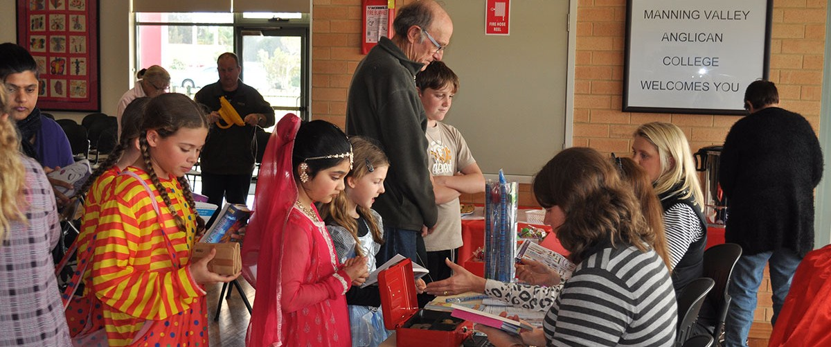 Students line up in costume to purchase books at a school community event